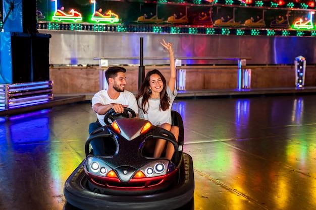Linda pareja divirtiéndose en autos chocadores