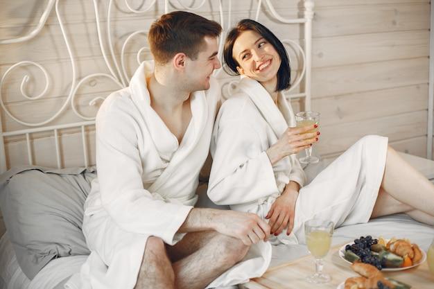 Linda pareja en el dormitorio con albornoces desayunando.