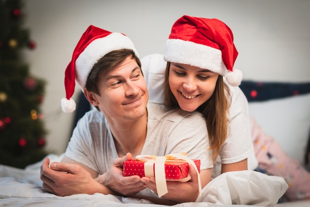 Linda pareja en dormitorio con regalo
