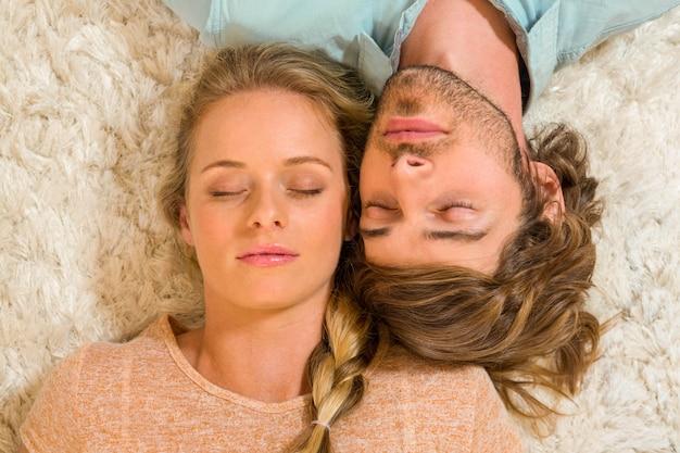 Linda pareja durmiendo en la alfombra en la sala de estar