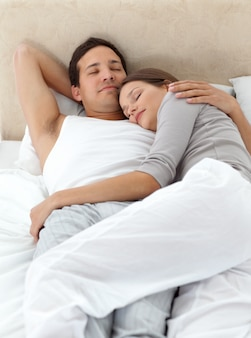 Linda pareja durmiendo en los brazos del otro en su cama
