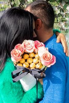 Linda pareja de enamorados abrazados mientras sostiene un ramo de rosas