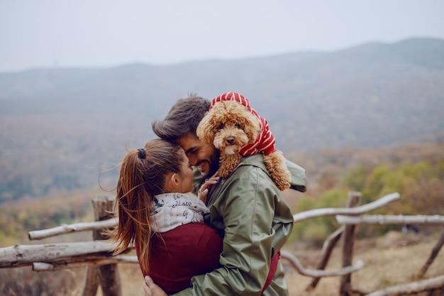 Linda pareja de enamorados de pie en la naturaleza y abrazos.