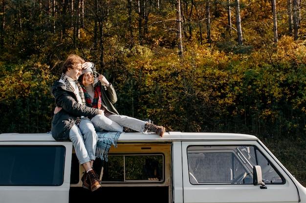Linda pareja estar cerca mientras está sentado en una camioneta con espacio de copia