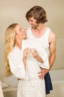 Linda pareja feliz de ver la prueba de embarazo positiva en el baño