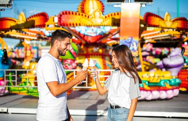 Linda pareja con helados en la feria