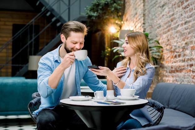 Linda pareja joven bebiendo café juntos, sentados a la mesa en el moderno loft cafe u hotel
