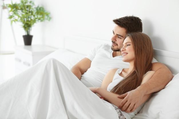 Linda pareja joven en la cama en casa