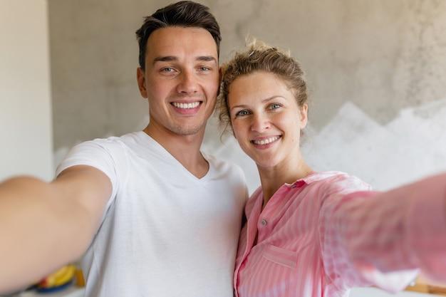 Linda pareja joven divirtiéndose en el dormitorio por la mañana, hombre y mujer haciendo foto selfie en pijama