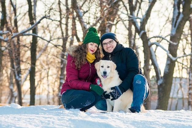 Linda pareja joven divirtiéndose en winter park con su perro golden retriever en un día soleado y sonriendo. mujer y hombre abrazando con perro en campo nevado de invierno