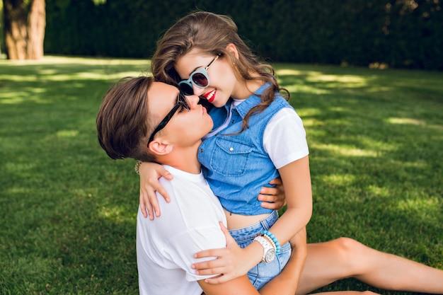 Linda pareja de jóvenes sobre césped en el parque. chica guapa con pelo largo y rizado en ropa de jeans está sentada sobre un chico guapo con camiseta blanca. intenta conseguir un beso.
