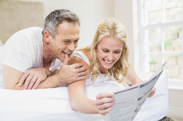 Linda pareja leyendo las noticias en la cama