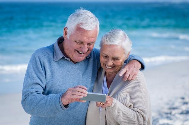 Linda pareja madura mirando smartphone