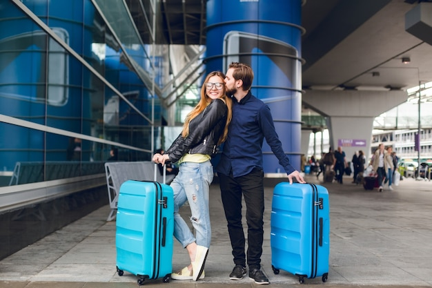 Linda pareja con maletas está de pie afuera en el aeropuerto. tiene cabello largo, lentes, suéter amarillo, chaqueta. viste camisa negra, barba. guy abraza y besa a la chica.