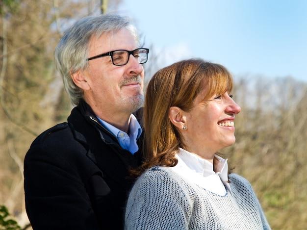 Linda pareja de mediana edad abrazando al aire libre