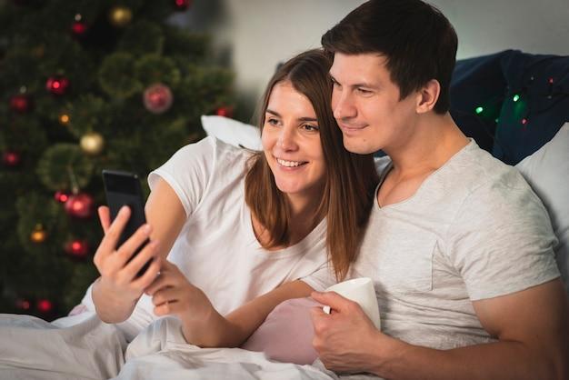Linda pareja mirando el teléfono en la cama