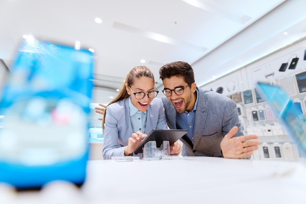 Linda pareja multicultural en ropa formal sonriendo y buscando una nueva tableta para comprar. interior de la tienda de tecnología.