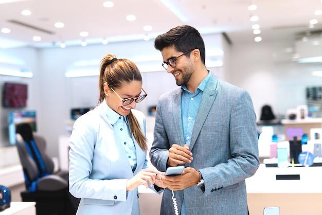 Linda pareja multicultural vestida con un traje de elegir teléfono inteligente. interior de la tienda de tecnología.