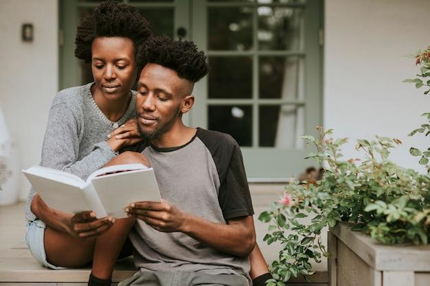 Linda pareja negra leyendo un libro juntos en un jardín.