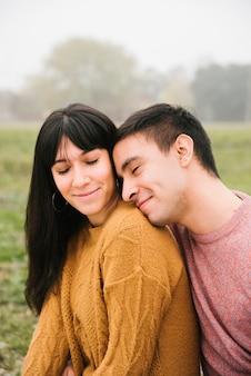 Linda pareja de ojos cerrados sonriendo y abrazando en el parque
