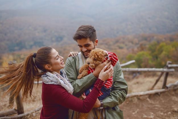 Linda pareja de pie en la naturaleza y jugando con su perro amoroso