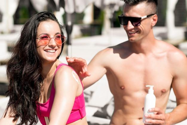 Linda pareja en la playa con protector solar