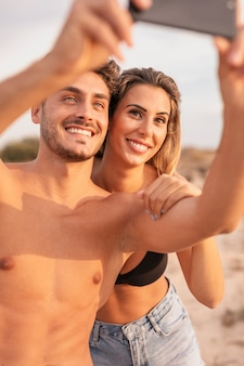 Linda pareja en la playa tomando selfie
