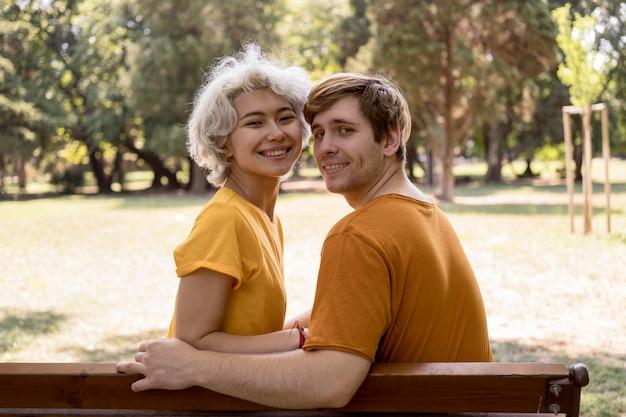 Linda pareja posando en un banco en el parque