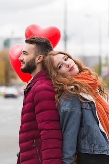 Linda pareja posando espalda con espalda