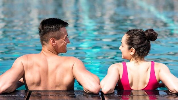 Linda pareja relajante en la piscina