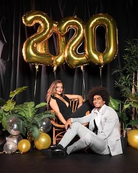 Linda pareja rodeada de globos con 2020 año nuevo