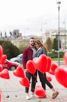 Linda pareja rodeada de globos de corazón