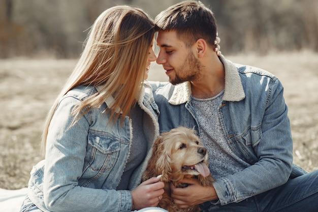 Linda pareja en ropa de jeans en un campo de primavera