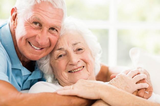 Linda pareja senior abrazando en el sofá