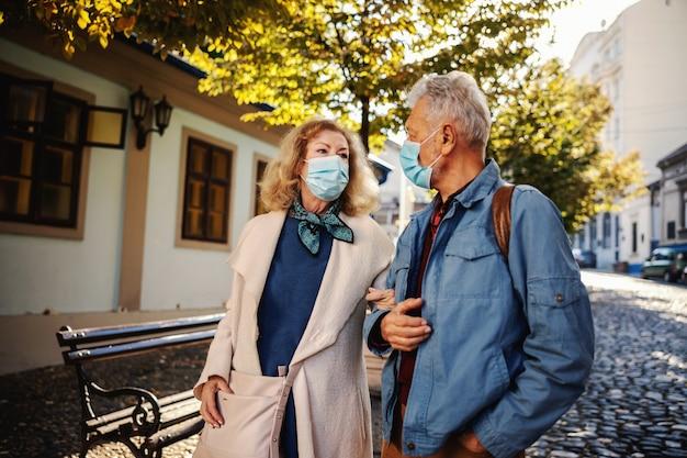 Linda pareja senior con máscaras protectoras caminando juntos en una parte antigua de la ciudad.