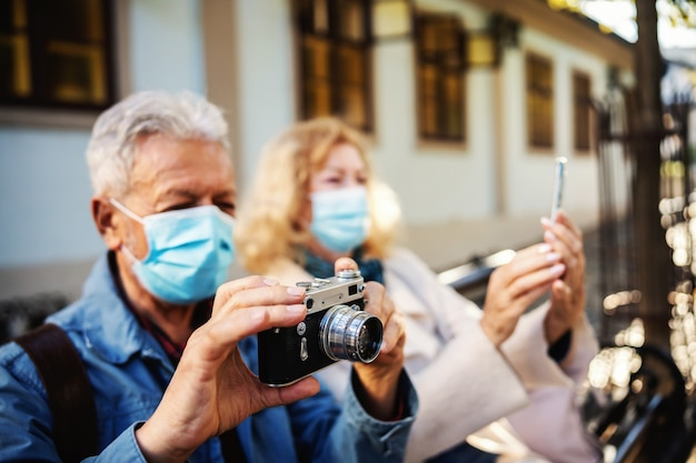 Linda pareja senior sentada en el banco y utilizando diversas tecnologías para tomar una foto.