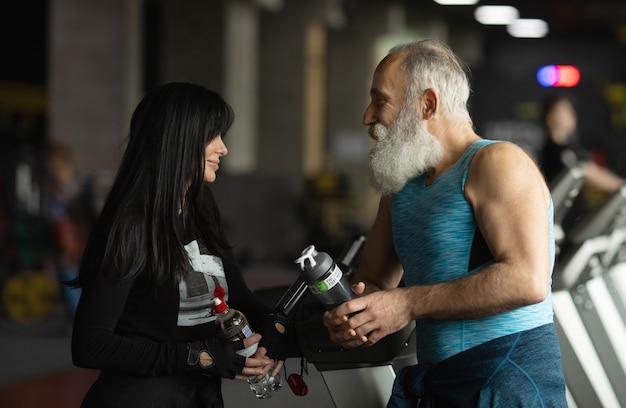 Linda pareja senior sonriente haciendo ejercicio en el gimnasio.