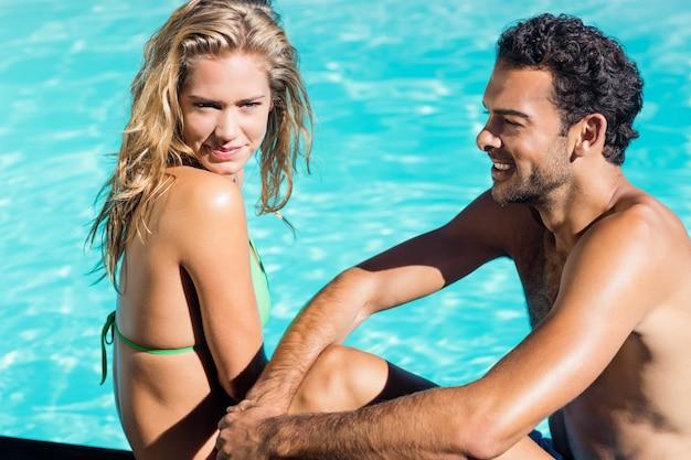 Linda pareja sentada al borde de la piscina