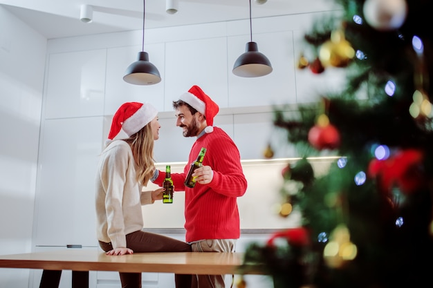 Linda pareja con sombreros de santa en la cabeza bebiendo cerveza y hablando en la cocina
