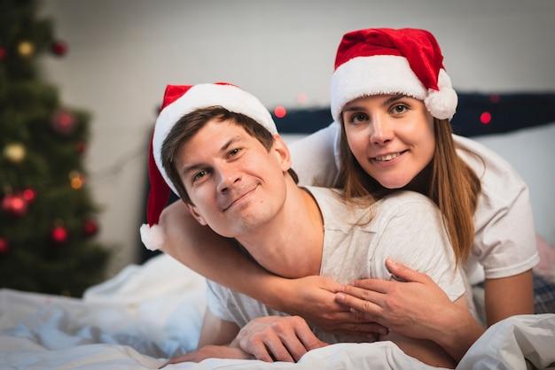 Linda pareja con sombreros de santa en la cama