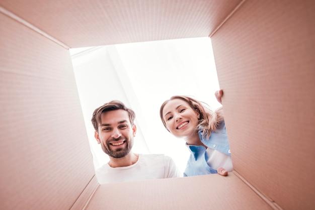 Linda pareja sonriente dentro de la parte inferior de la vista de caja