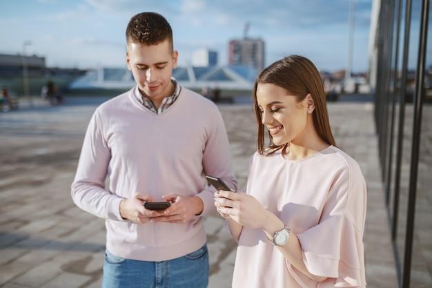 Linda pareja sonriente vestida elegante usando teléfonos inteligentes al aire libre
