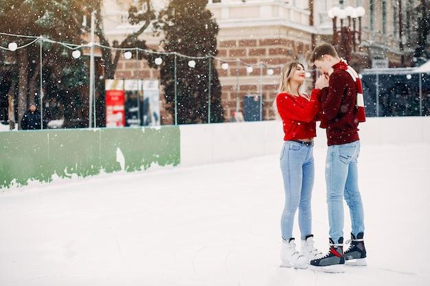 Linda pareja en un suéter rojo divirtiéndose en una arena de hielo