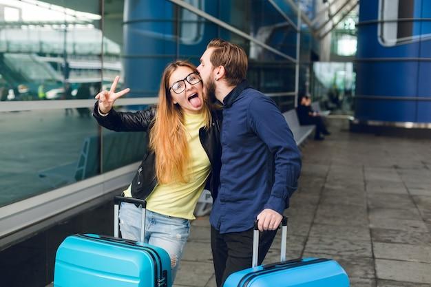 Linda pareja con sutcases está de pie afuera en el aeropuerto. tiene cabello largo, lentes, suéter amarillo, chaqueta. viste camisa negra, barba. se abrazan y simulan juntos.