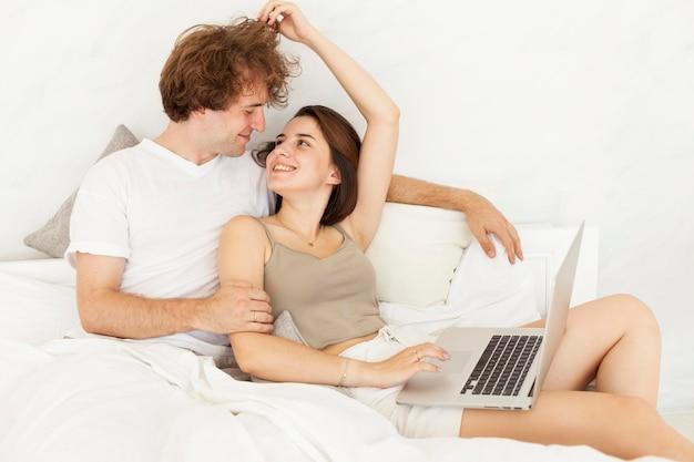 Linda pareja tendido en la cama juntos