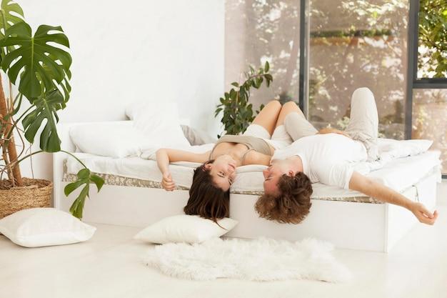 Linda pareja de tiro completo tendido en la cama juntos