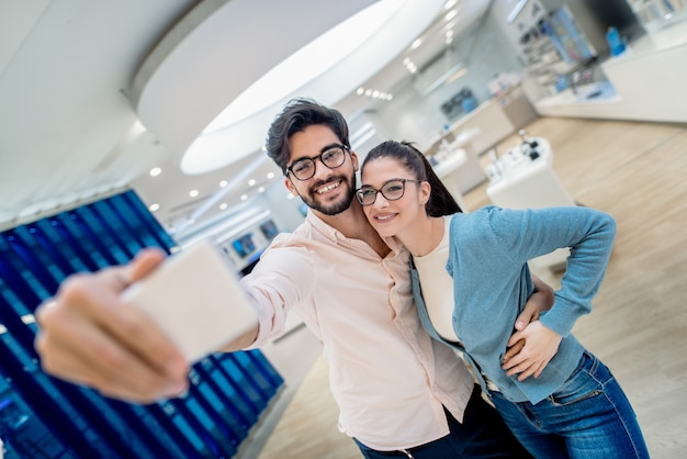 Linda pareja tomando autorretrato y abrazos mientras está de pie en la tienda de tecnología. concepto de nuevas tecnologías.