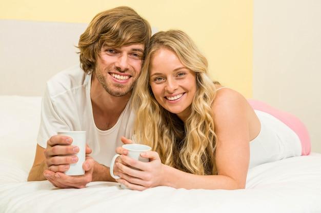 Linda pareja tomando un café acostado en su cama
