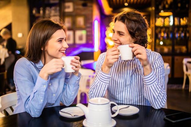 Linda pareja tomando café o té juntos en la cafetería
