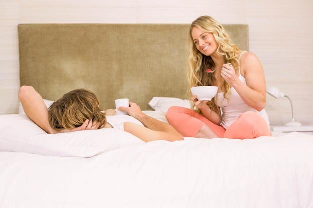 Linda pareja tomando un café en su cama en el dormitorio